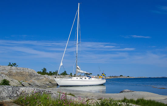 Sailboat moored at small rocky island in the outer part of the archipelago of Stockholm, Sweden